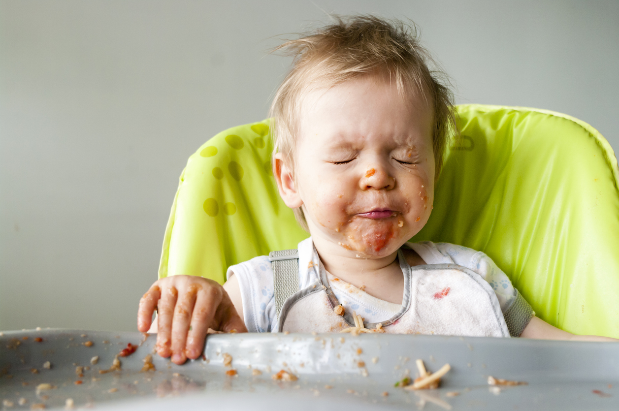 Toddler makes a mess as they sample new foods at dinnertime