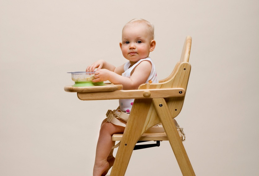 Baby in high chair eating solid food